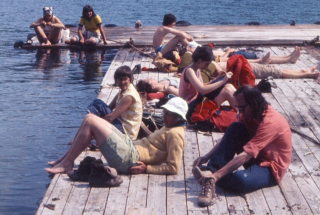 Aileen (left) cooling her feet at the Aylmer boat dock after a hike to the lookout ridge with Jon Whyte (right) and a group of Banff Centre students in June 1973. Brian Patton photo.